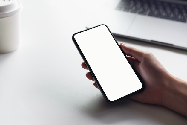 Woman holding smartphone mockup of blank screen on the table. Premium Photo