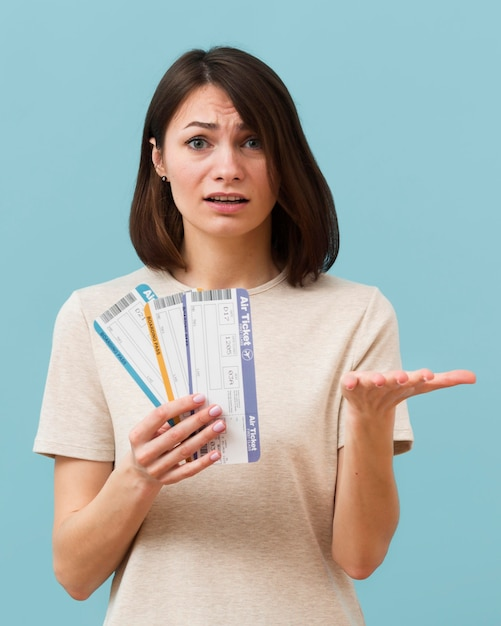 Woman holding some airplane tickets looking concerned Free Photo