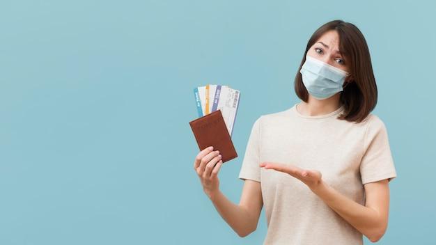 Женщина держит некоторые билеты на самолет во время ношения медицинской маски Premium Фотографии
