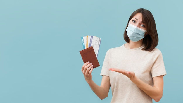 Woman holding some airplane tickets while wearing a medical mask Premium Photo