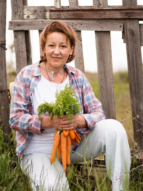 Woman holding some carrots in her hand Free Photo
