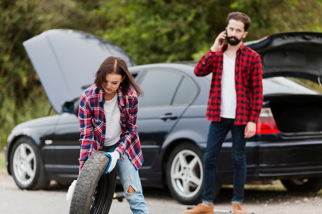 Woman holding spare tire and man talking on phone Free Photo