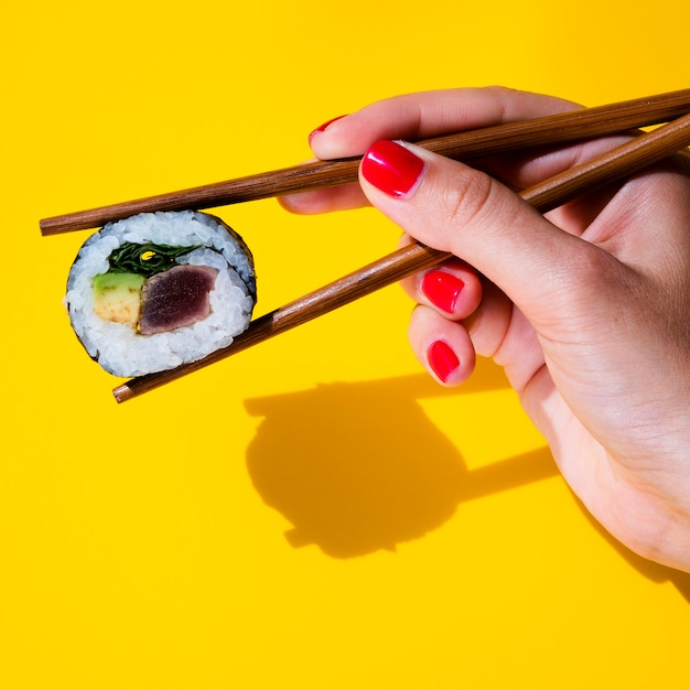 Woman holding a sushi roll in chopsticks on yellow background Free Photo