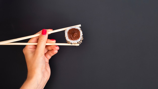 Woman holding a sushi roll with chopsticks on a grey backgrund Free Photo