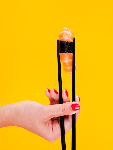 Woman holding a sushi on yellow bacground Free Photo