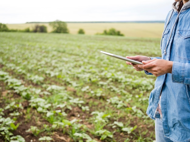 Woman holding a tablet next to a farm field with copy space Free Photo