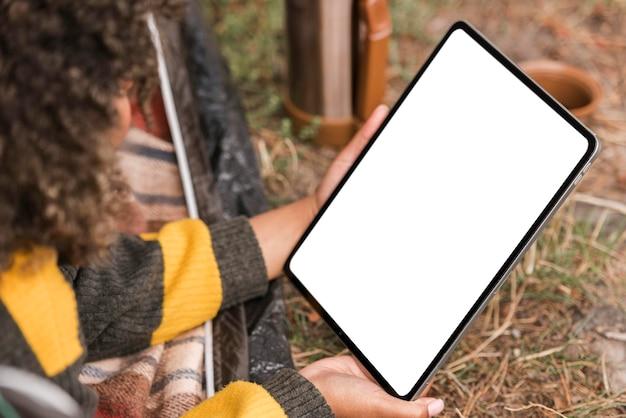Женщина, держащая планшет во время кемпинга на открытом воздухе Бесплатные Фотографии