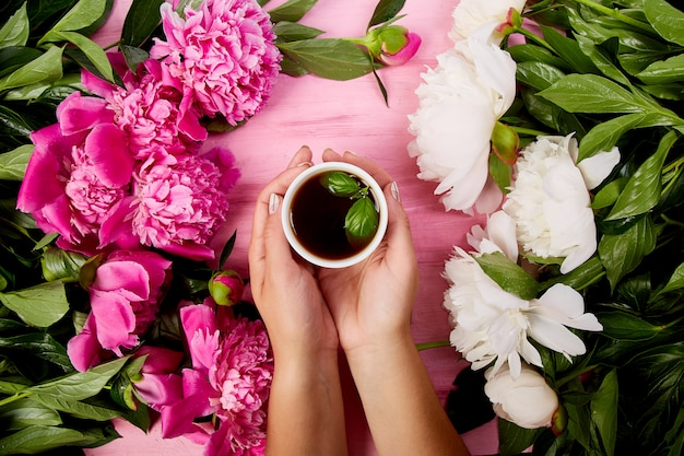 Woman holding tea cup surrounded by flowers Premium Photo