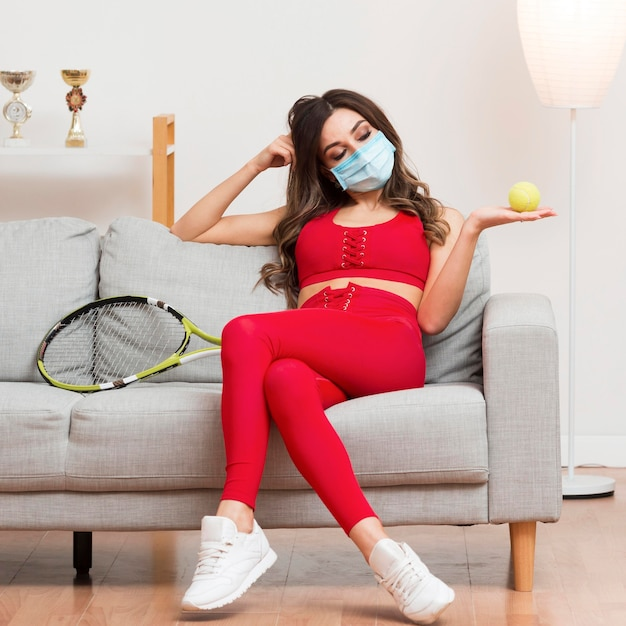 Woman holding a tennis ball while wearing a medical mask Free Photo