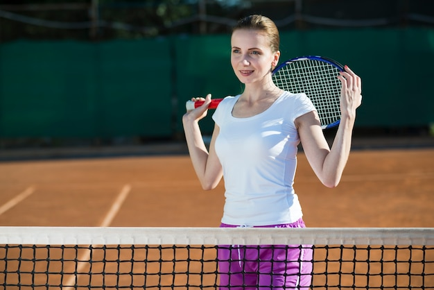 Woman holding tennis racket on the back Free Photo
