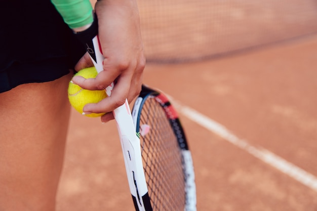 Woman holding tennis racket and ball on clay court. Free Photo