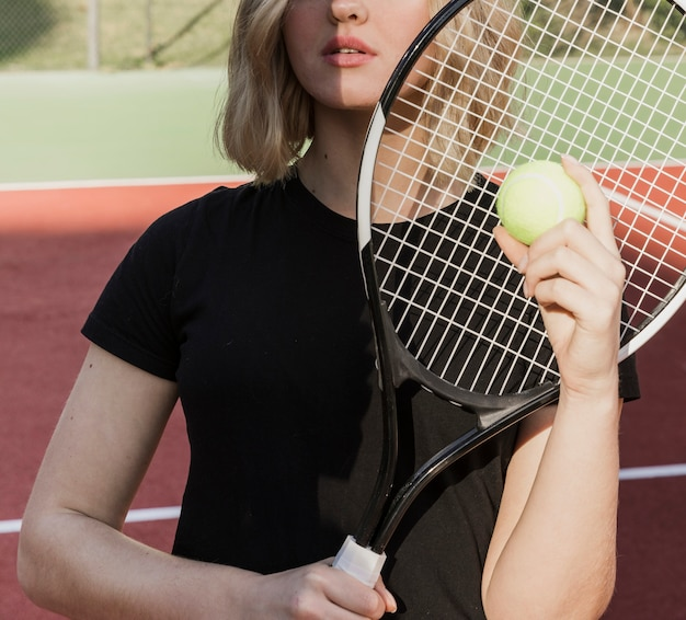 Woman holding tennis racket and ball Free Photo