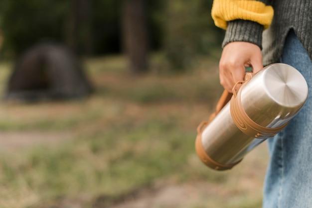 Женщина держит термос во время кемпинга с копией пространства Premium Фотографии