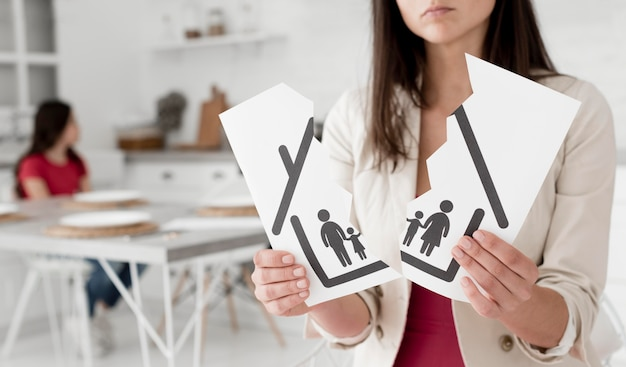 Woman holding torn apart family drawing Free Photo