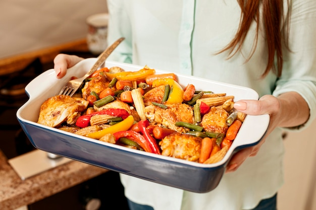 Woman holding tray of food for dinner Free Photo
