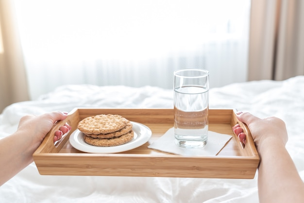 Woman holding tray with diet breakfast of crackers and water on a bed Premium Photo