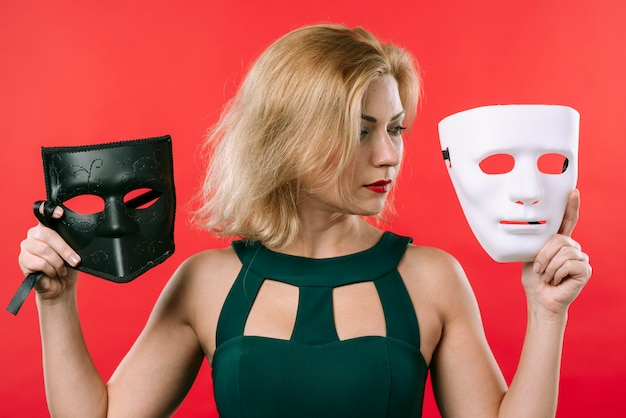 Woman holding two masks in hands Free Photo