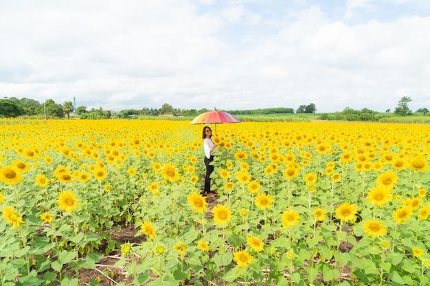 Woman holding an umbrella in a sunflower field. Premium Photo