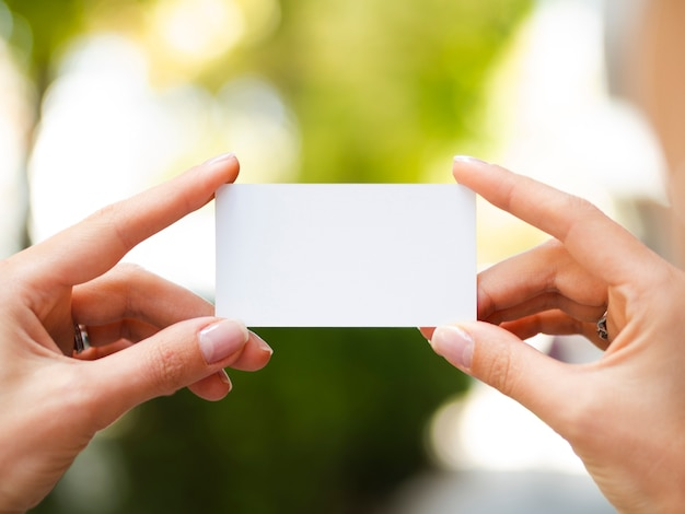 Woman holding up a business card mock-up Free Photo