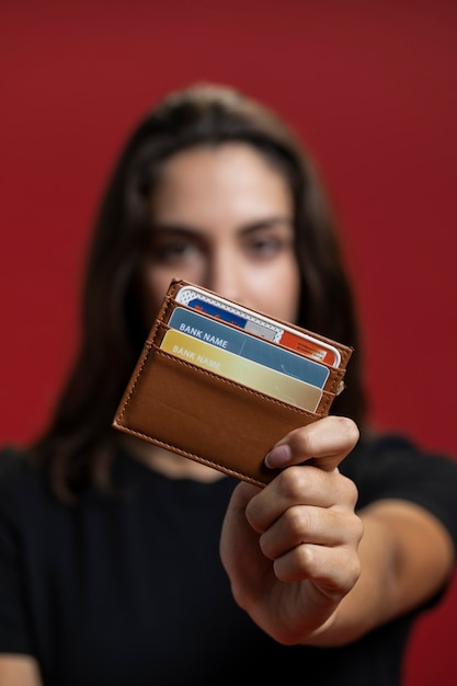 Woman holding up her wallet close-up Free Photo