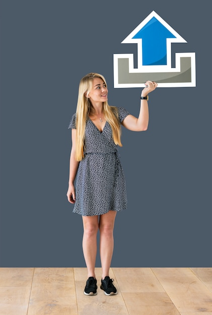 Woman holding an upload icon in a studio Free Photo