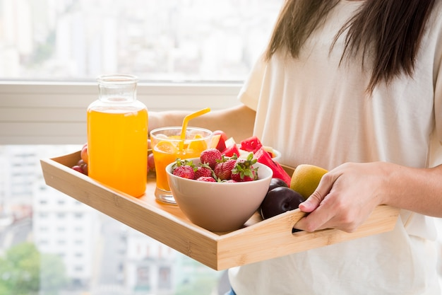 Woman holding various fruits and juice bottle on wooden tray Free Photo