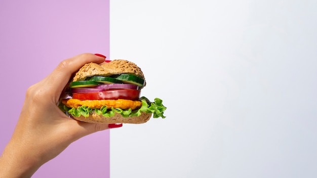 Woman holding a vegetable burger in her hand Free Photo