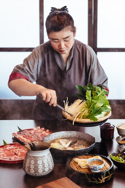A woman holding vegetables into hot pot by tongs with wagyu a5 beef and sliced kurobuta in shabu. Premium Photo