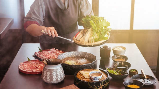 A woman holding vegetables into hot pot by tongs with wagyu beef and sliced kurobuta in shabu. Premium Photo