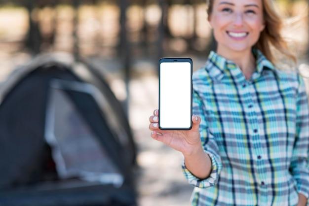 Женщина держит мобильный телефон вертикальной копии пространства Бесплатные Фотографии
