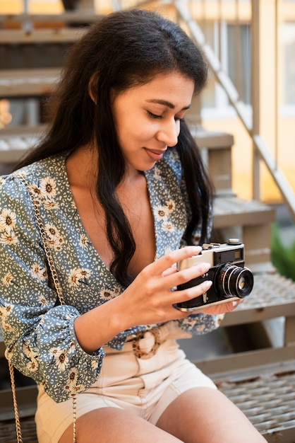 Woman holding a vintage camera and looking at photos Free Photo