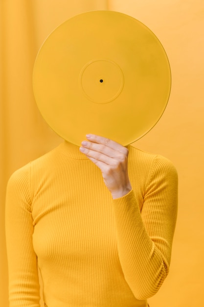 Woman holding vinyl in front of face in a yellow scene Free Photo