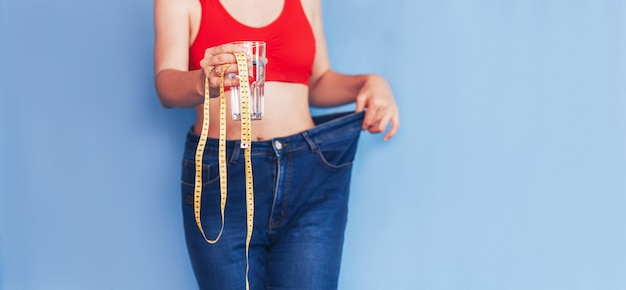 Woman holding water and measure tape Premium Photo