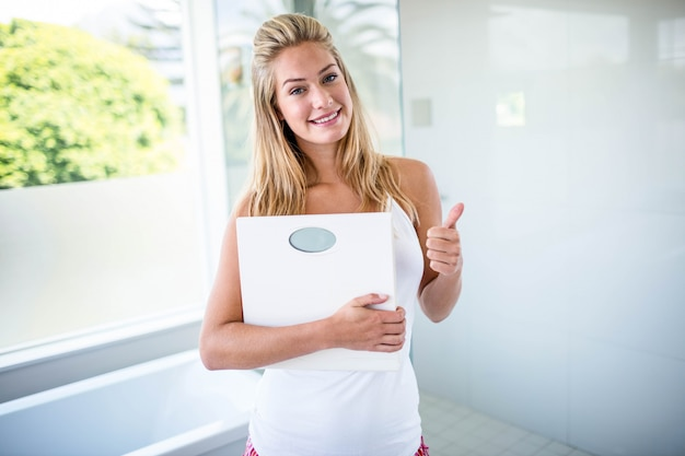 Woman holding a weighting scale with thumbs up in the bathroom Premium Photo