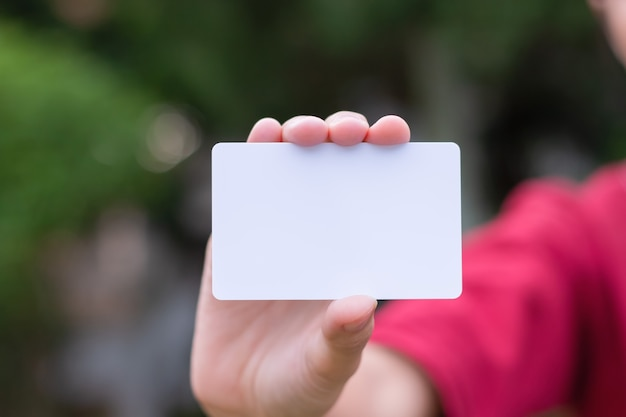 Woman holding white business card on natural bokeh background Premium Photo