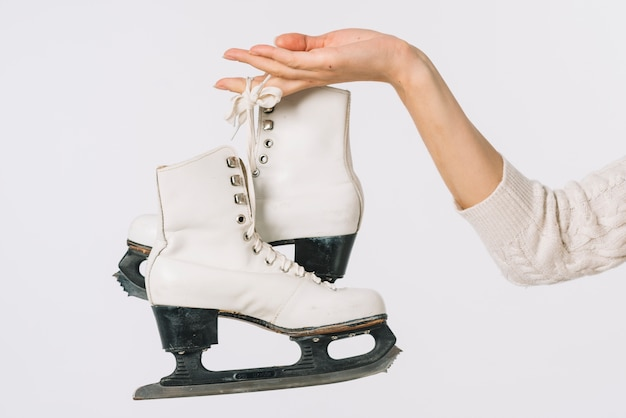 Woman holding white skates in hand Free Photo