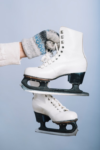 Woman holding white skates in hand Free Photo