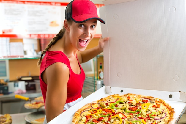 Woman holding a whole pizza in hand Premium Photo