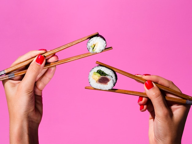 Woman holding with both hand sushi rolls on chopsticks Free Photo