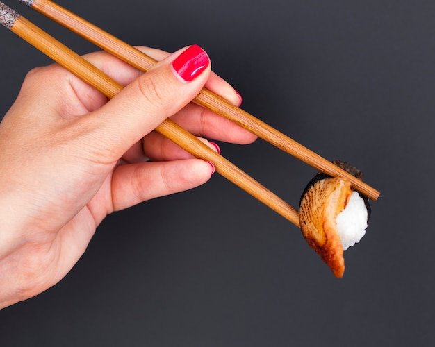 Woman holding in wooden chopsticks a sushi Free Photo