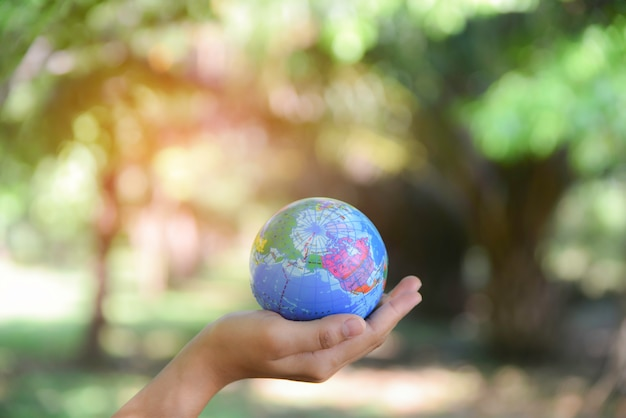 Woman holding world ball on her hand with natural green background. world environment day concept. Premium Photo