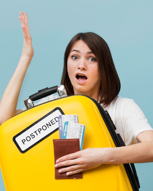 Woman holding a yellow baggage with a postponed sign while holding airplane tickets Free Photo