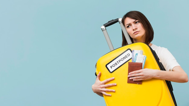 Woman holding a yellow baggage with a postponed sign with copy space Free Photo