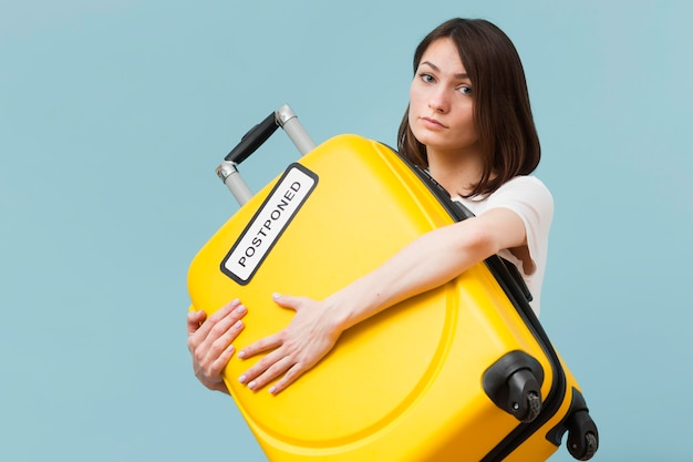 Woman holding a yellow baggage with a postponed sign Free Photo