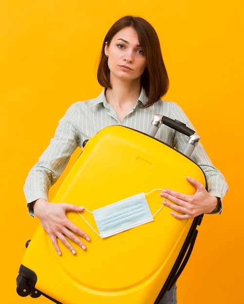 Woman holding a yellow luggage and a medical mask Premium Photo