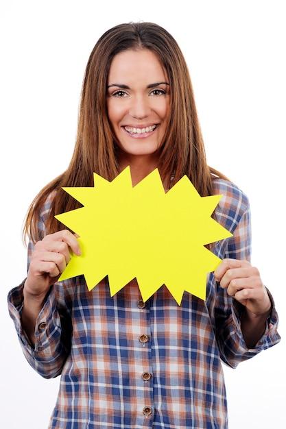 白い背景で隔離の黄色のパネルを保持している女性 無料写真
