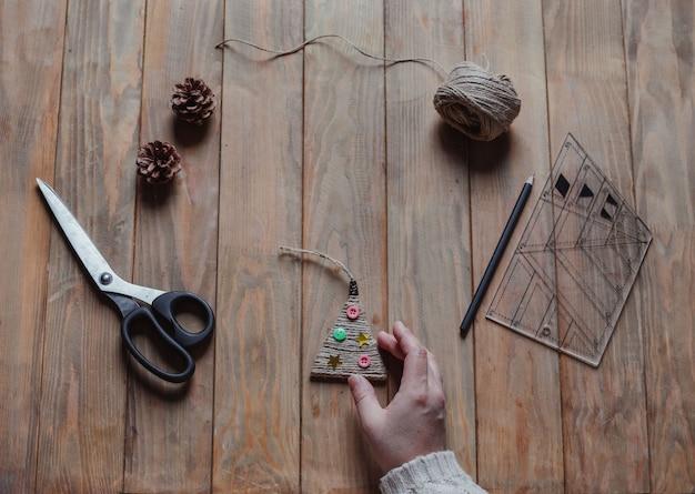 여자는 그녀의 손에 수 제 크리스마스 트리 장난감을 보유 프리미엄 사진