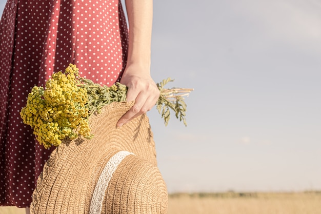 Woman holds bunch of field flowers and a hat. rural scene: close-up view of female in polka-dot dress with farmer hat and bouquet in her hand Premium Photo