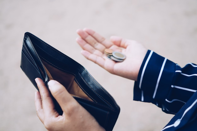 Woman holds an empty purse and coins in hand meaning money financial problem or bankrupt jobless, broke after credit card payday jobless, debt concept. Premium Photo
