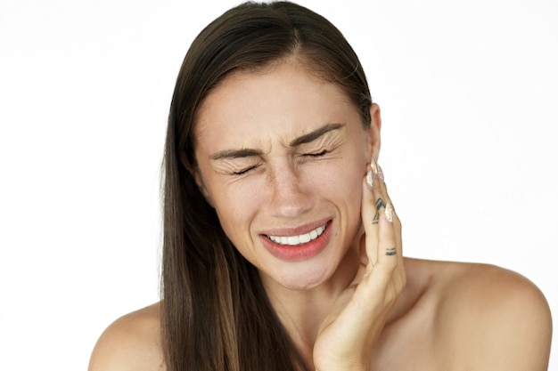 Woman holds fingers on her cheek showing toothache Free Photo